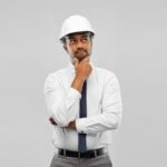 indian male architect in helmet over grey