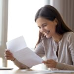 Happy excited woman reading letter with good news, great offer